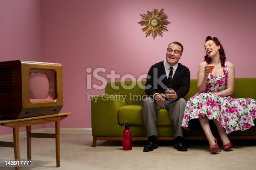 retro couple laugh at their tv set