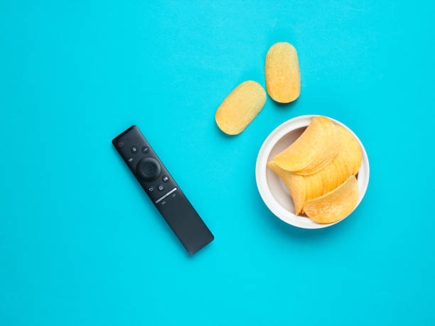 Tv remote, potato chips in a plate on bue background. Watching TV, top view stock photo