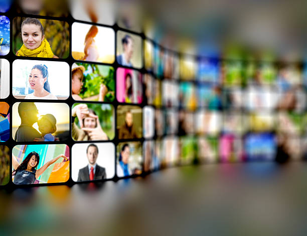 tv screens with video stills showing many people stock photo