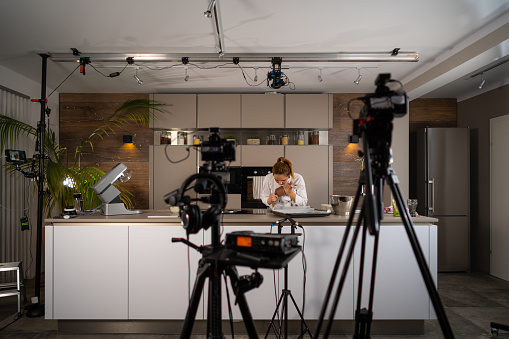 food vlogger v-logger blogger influencer woman recording video vlog vlogging in tv-show studio kitchen for social media behind the scenes film and audio equipment visible