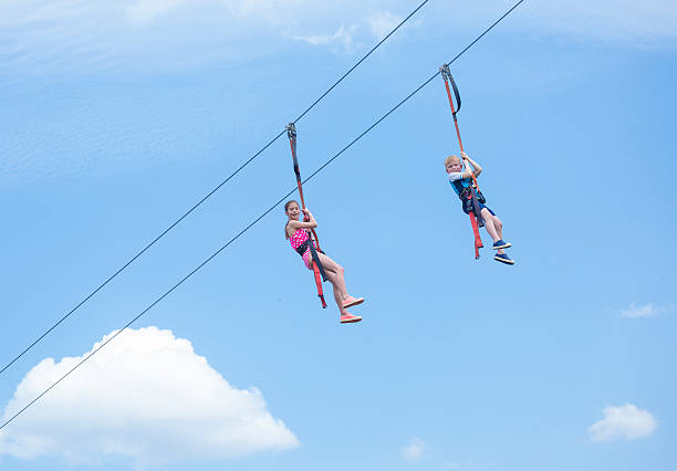Tw kids playing on a zip line view from below Two happy kids enjoying a fun ride on a zip line high above the ground. View from below with simple blue sky in the background zip line stock pictures, royalty-free photos & images