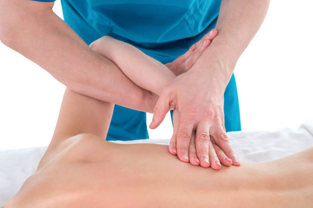 Tween age girl's shoulder being manipulated by osteopathic or chiropractic manual therapist or physician - medical massage concept stock photo