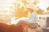 Young tween cowgirl smiling at something off camera and waiting on her horse at a summer evening rodeo in Utah.