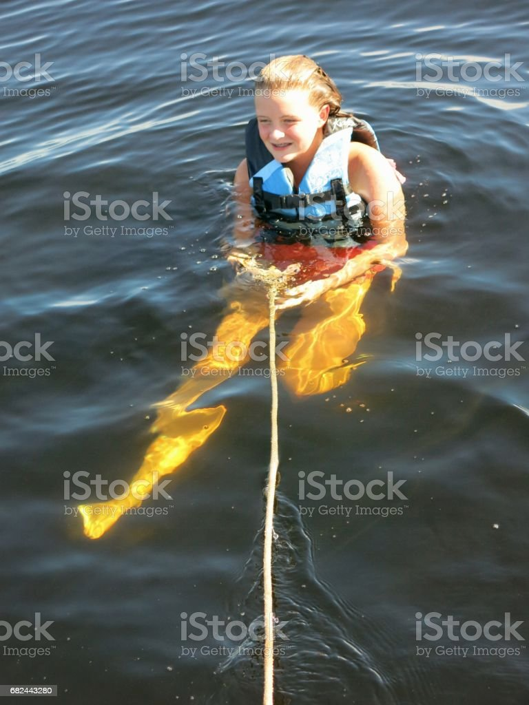 Tween Girl Wearing Lifejacket Swimming in Lake Holding Rope royalty-free stock photo