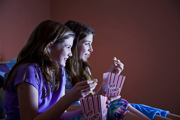 tween mädchen vor dem fernseher - mädchen night snacks stock-fotos und bilder