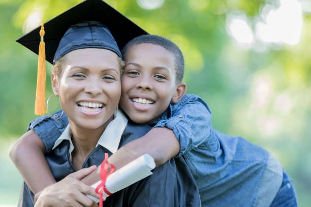 Tween son poses with mom after her college graduation ceremony stock photo