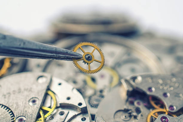 tweezers and detail of mechanical watches stock photo
