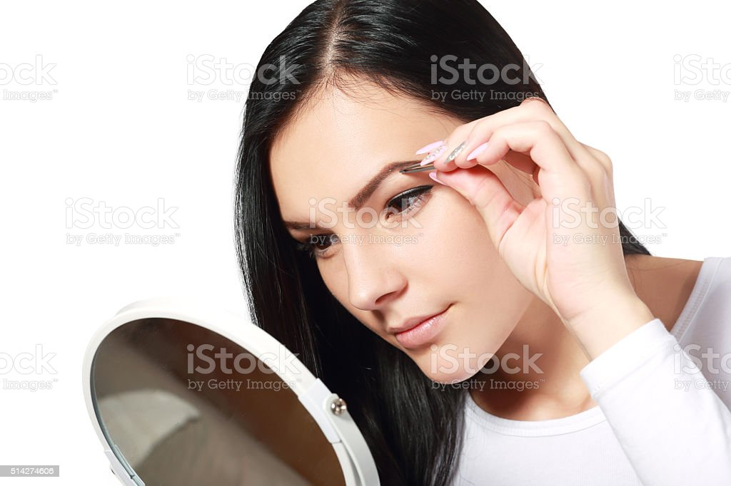 tweezing eyebrow stock photo