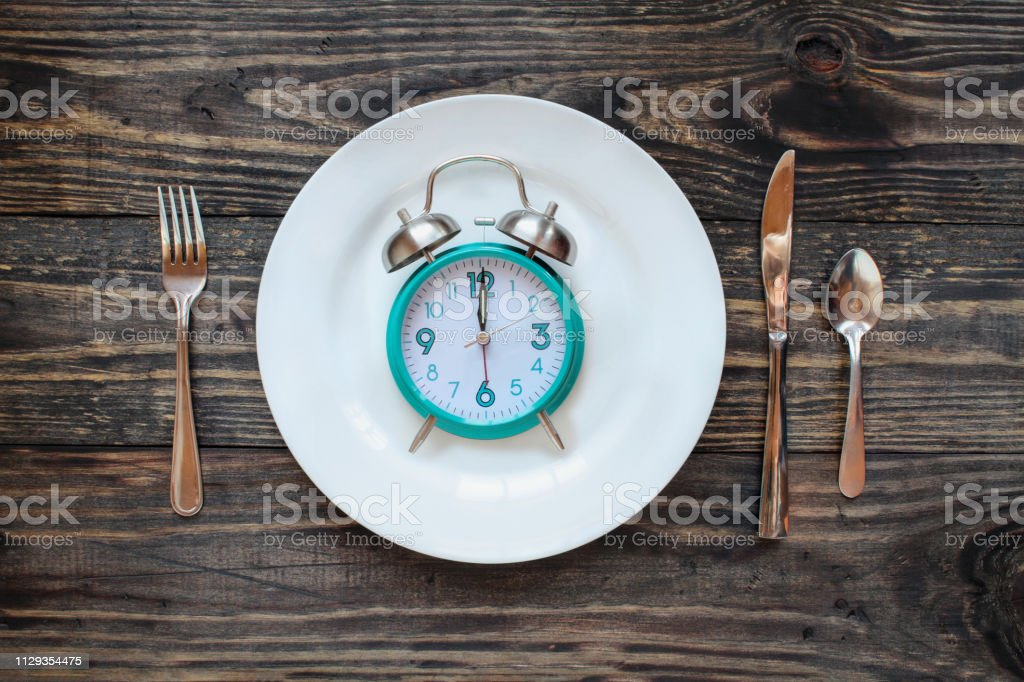 Twelve hour intermittent fasting time concept with clock on plate stock photo