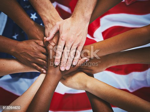A dozen mixed hands stacked up on top of the American national flag.