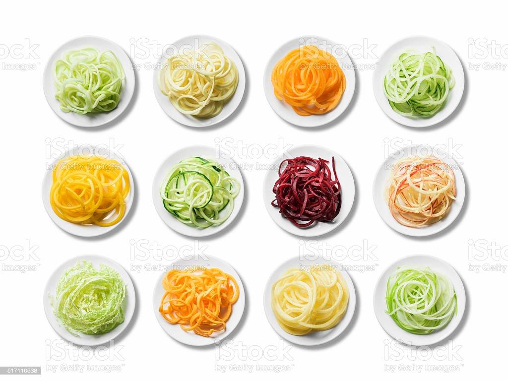 Twelve plates of fresh, bright spiralised fruit and vegetables stock photo