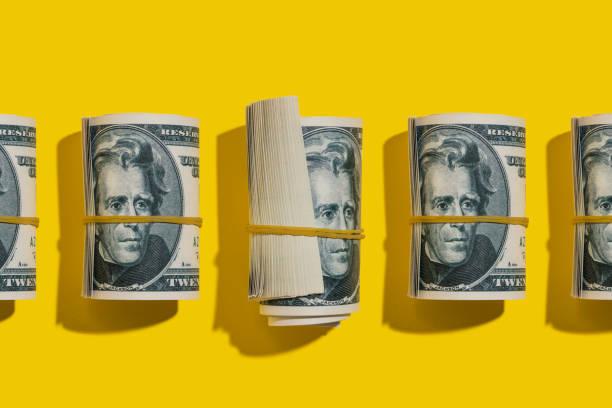 Twenty dollar rolls flat lay on yellow background stock photo