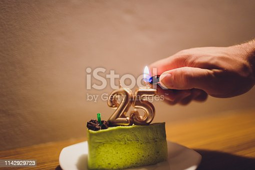 178269167istockphoto Twenty five years anniversary. Birthday chocolate cake with white burning candles in the form of number Twenty five. Dark background with black cloth. 1142929723