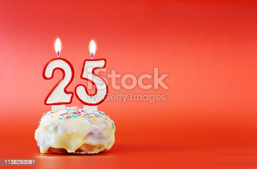 Twenty five years birthday. Cupcake with white burning candle in the form of number 25. Vivid red background with copy space