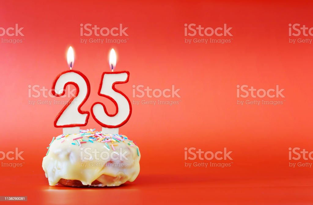 Twenty five years birthday. Cupcake with white burning candle in the form of number 25. Vivid red background with copy space stock photo