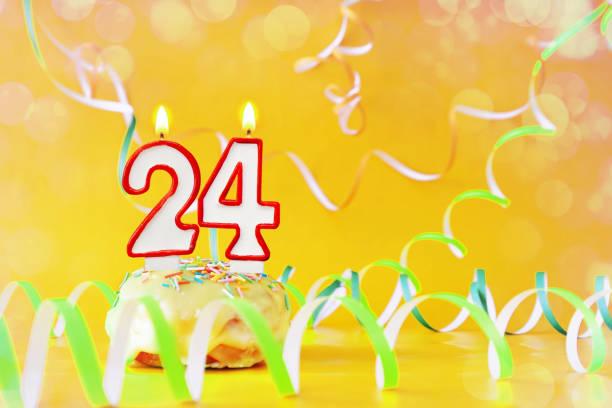 vingt-quatre ans d'anniversaire. cupcake avec des bougies brûlantes sous la forme du numéro 24. fond jaune vif avec l'espace de copie - nombre 24 photos et images de collection