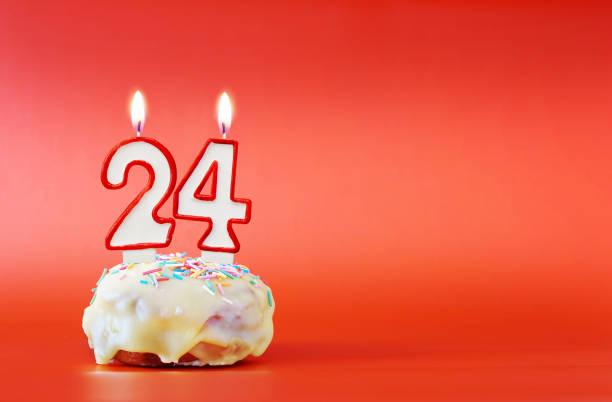 vingt-quatre ans d'anniversaire. cupcake avec la bougie brûlante blanche sous la forme du numéro 24. fond rouge vif avec l'espace de copie - nombre 24 photos et images de collection