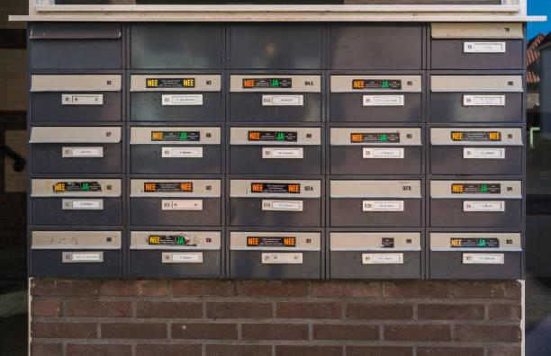 eenentwintig postvakken van een appartement gebouw met diverse stickers (ja-nee) te zeggen wat voor soort folders en kranten ze willen - netherlands map stockfoto's en -beelden