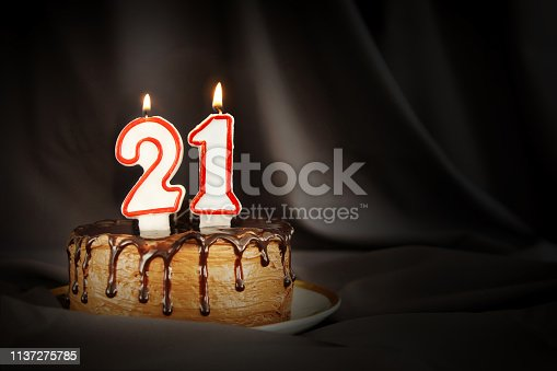 Twenty one years anniversary. Birthday chocolate cake with white burning candles in the form of number Twenty one. Dark background with black cloth