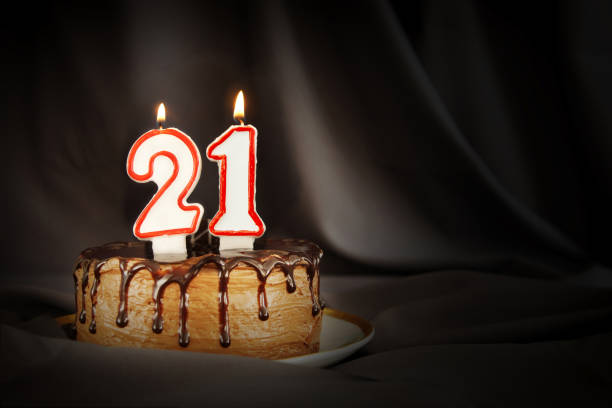 twenty one years anniversary. birthday chocolate cake with white burning candles in the form of number twenty one. dark background with black cloth - number 21 stock photos and pictures