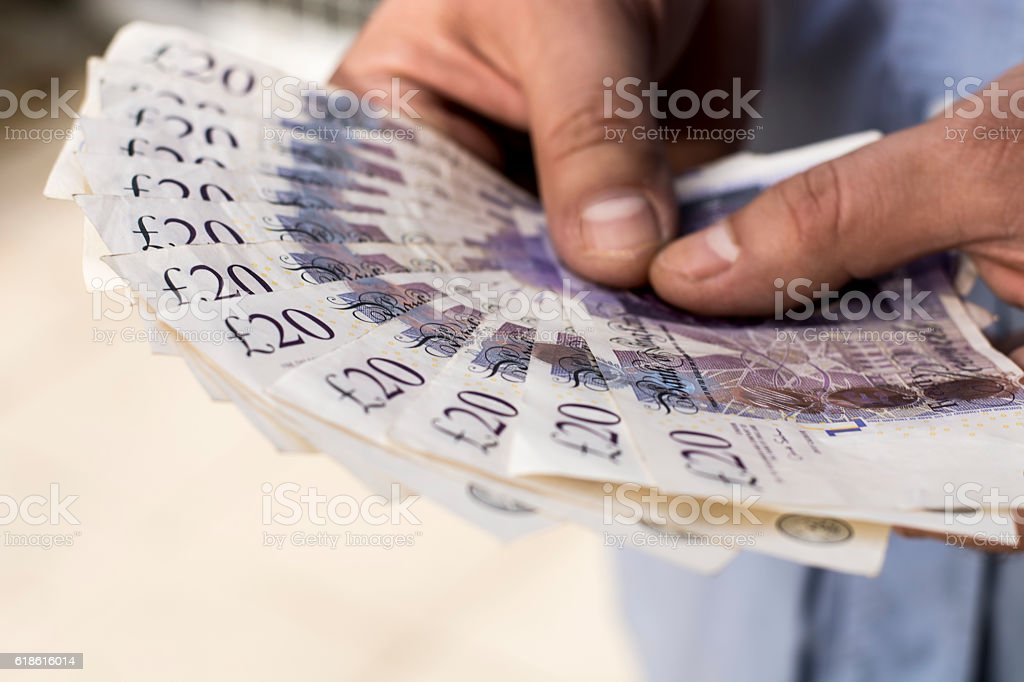 Twenty pound banknotes in man's hands stock photo