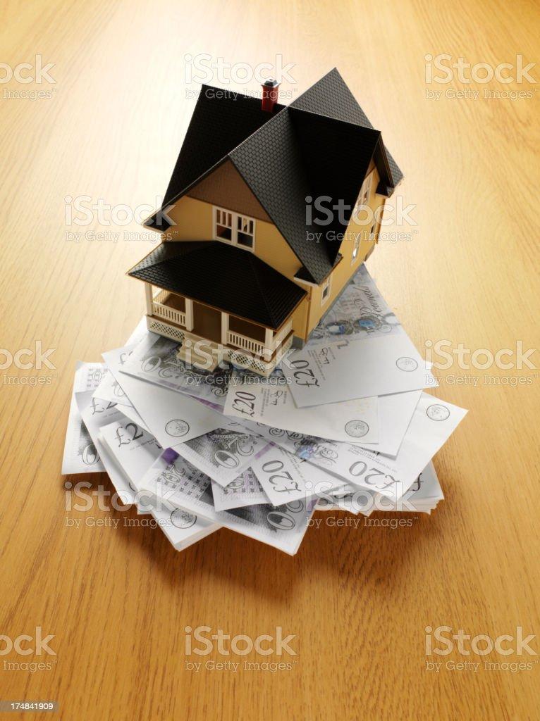 Twenty Pound Notes Under a Model Toy House royalty-free stock photo