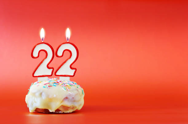 Twenty two years birthday. Cupcake with white burning candle in the form of number 22. Vivid red background with copy space stock photo