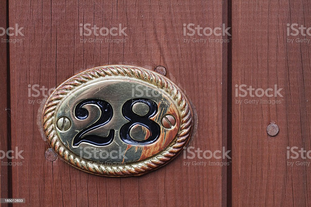 Twenty-eight metal number 28 on wooden gate stock photo