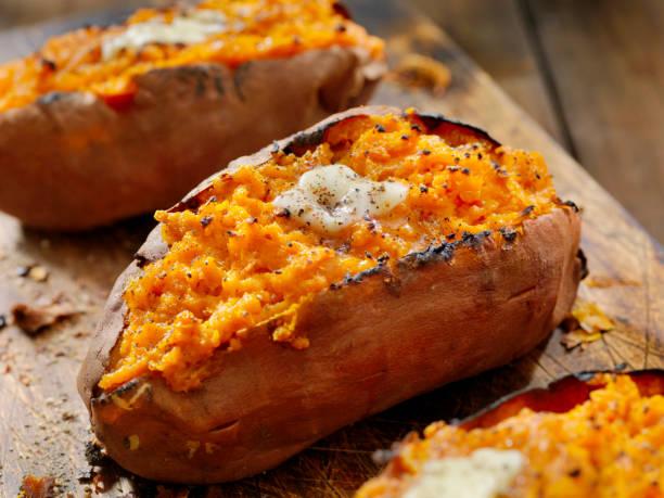 dwa razy pieczone, nadziewane słodkie ziemniaki z topiącym się masłem i pękniętym pieprzem - słodki ziemniak zdjęcia i obrazy z banku zdjęć