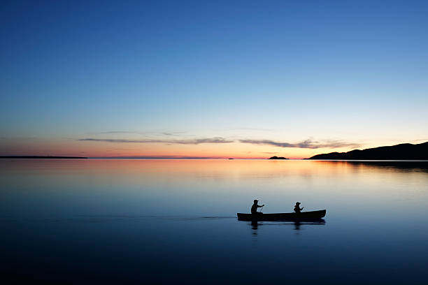 XL twilight canoeing father and son in silhouette conoeing at twilight (XL) wisconsin stock pictures, royalty-free photos & images