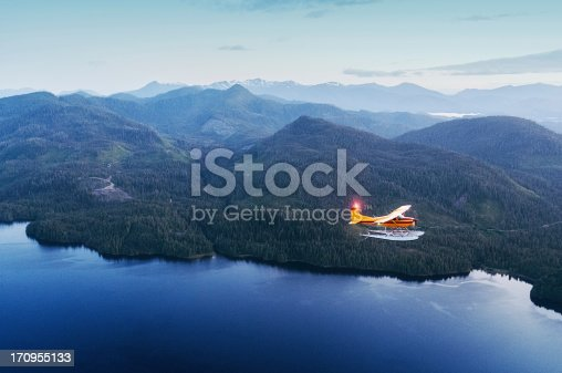 A seaplane flies over Southern Alaska in twilight.  Shot at high iso with slight grain.