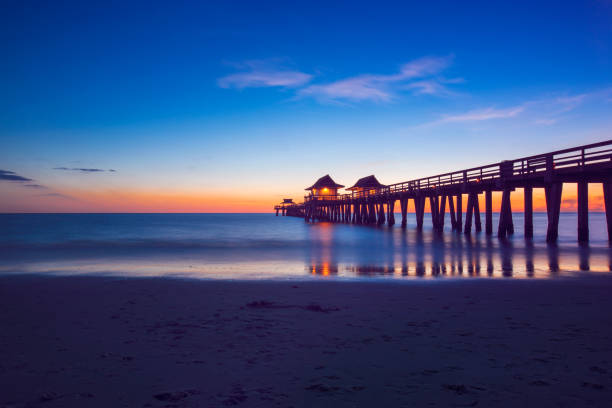Twilight Hour at the Naples Pier in Naples, Florida Color image of the Naples Pier in beautiful Naples, Florida right after a sunset on the beach. naples florida stock pictures, royalty-free photos & images