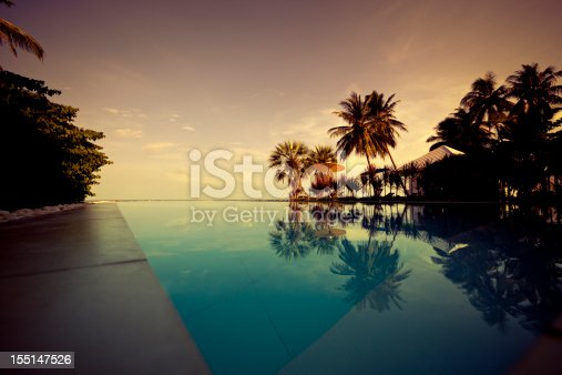 tropical sunset swimming pool scene with palm tree silhouettes at koh samui, thailand.