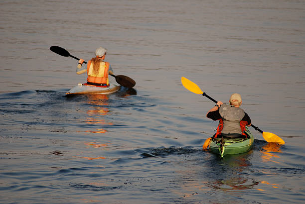 Twilight Kayak Paddlers, Great Slave Lake, Northwest Territories. stock photo