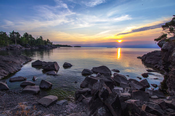 Twilight Over The Blue Water Of The Rugged Lake Superior Coast With A Small Island In Copper Harbor Michigan stock photo