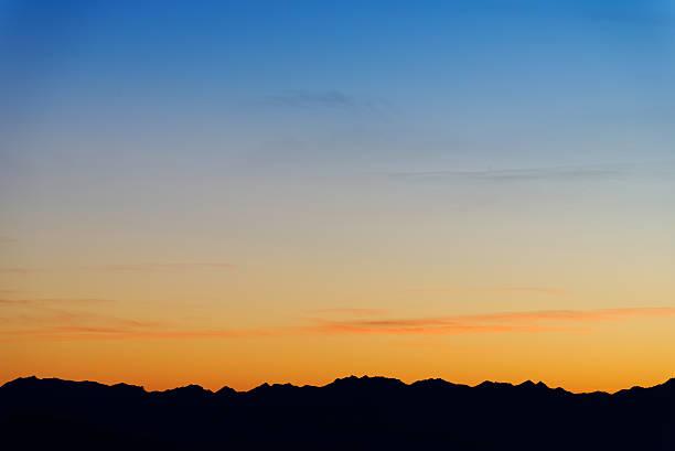 Twilight sky colors over mountain range on horizon stock photo