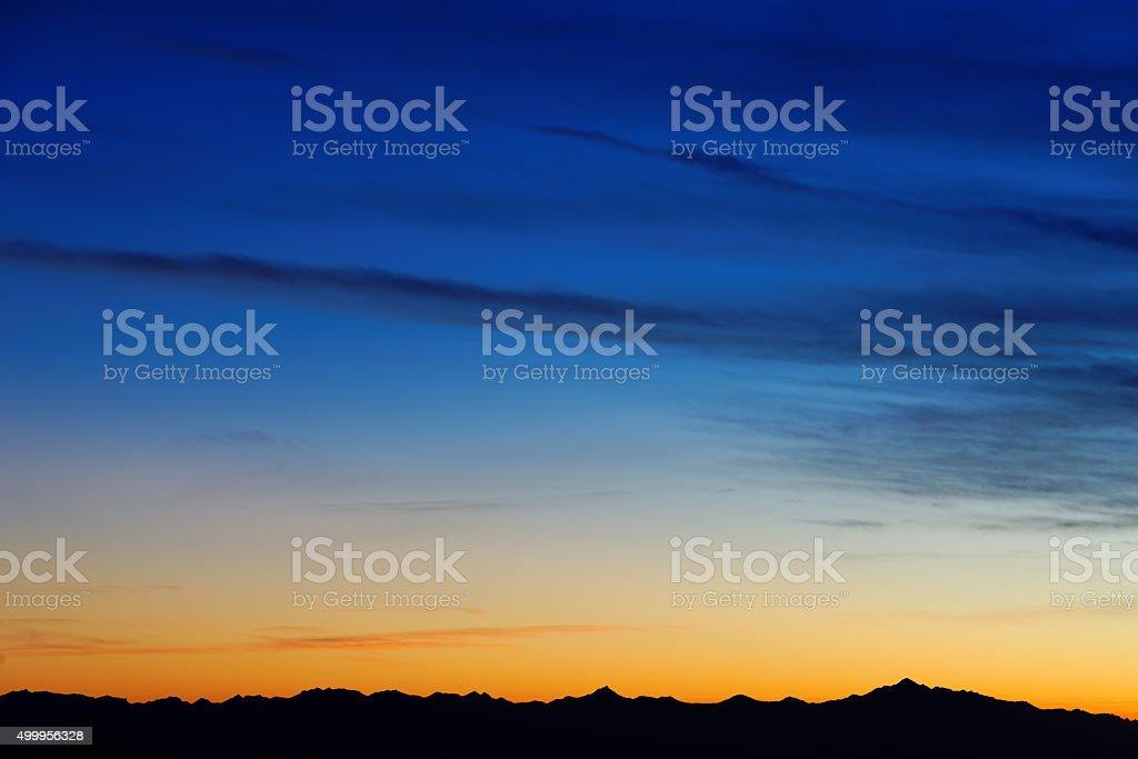 Twilight sky colors over mountain range on horizon (few clouds) stock photo