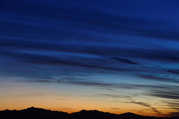 Twilight sky colors over mountain range on horizon (more clouds) stock photo