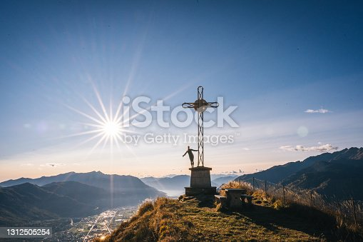 istock Twilight view of woman on summit cross above valley and mountains 1312505254