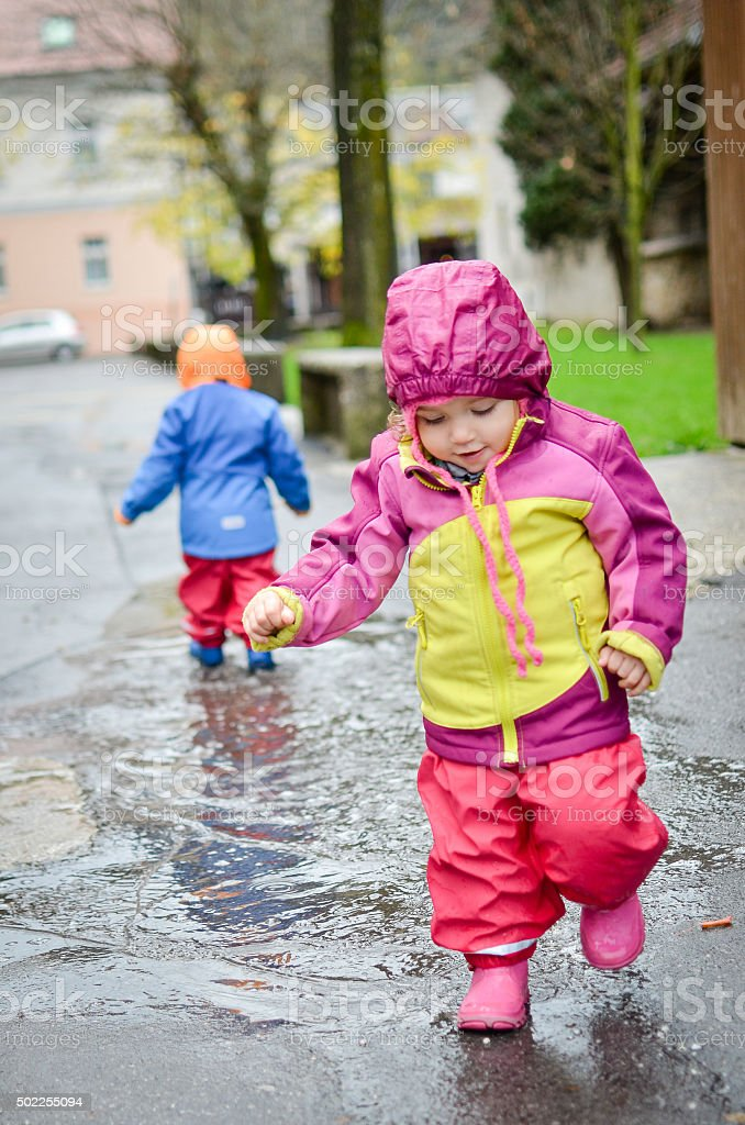 Twin babies in rain clothes stock photo