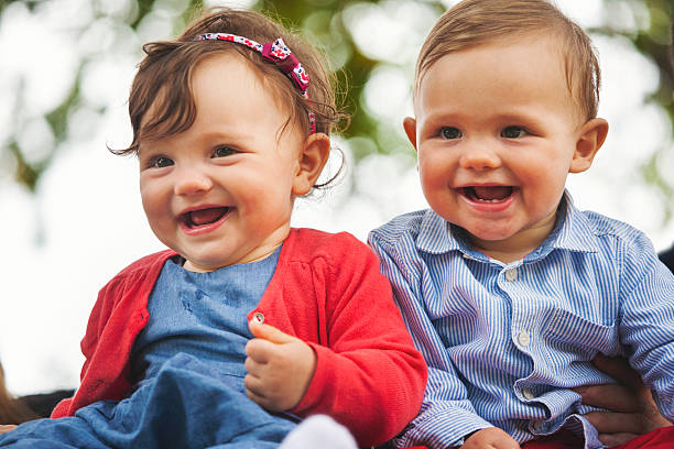Twin baby smiling for the camera stock photo