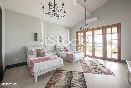 Modern hotel room with two beds and french doors with natural light, ethnic floor covering on tiled floor