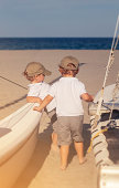 Twin boys are taking a break from sailing. Hanging on the sailboat on the beach