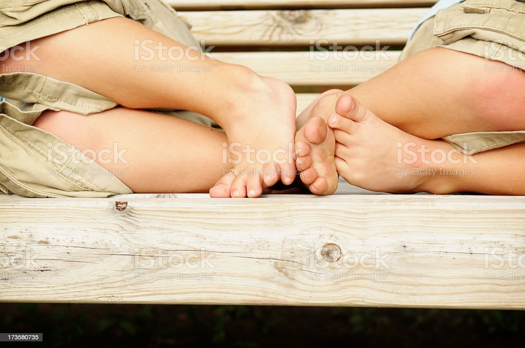 Twin Boys Feet On A Wooden Bench Royalty Free Stock Photo