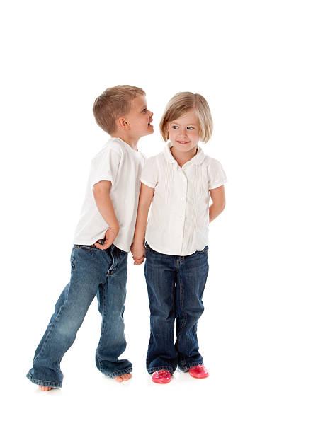 Twin Brother and Sister Children Whisper Secret Full Length stock photo