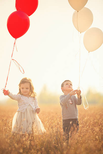 Twin brother and sister holding balloons outdoor stock photo