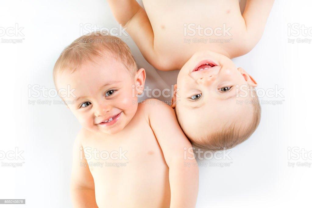 Twin brother having fun on a studio white floor stock photo
