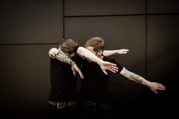 twin brothers doin the dab dance figure stock photo
