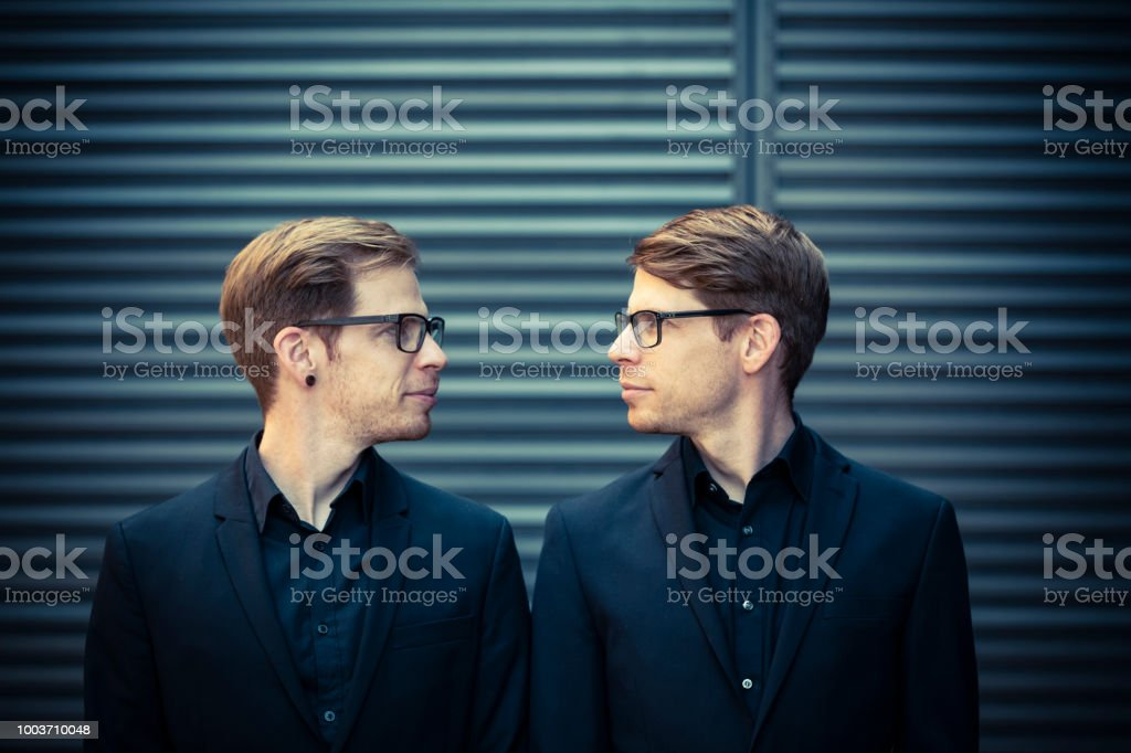 twin brothers face to face portrait stock photo