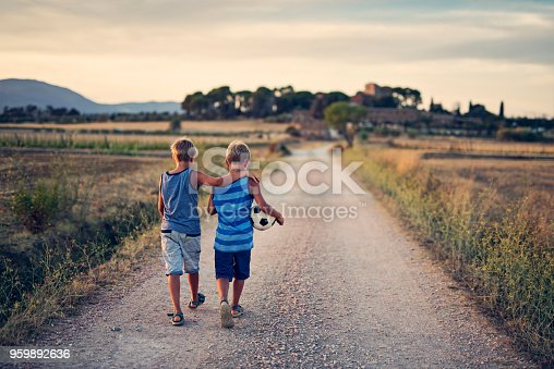 Twin brothers returning home after playing soccer. Rural country road. Nikon D810